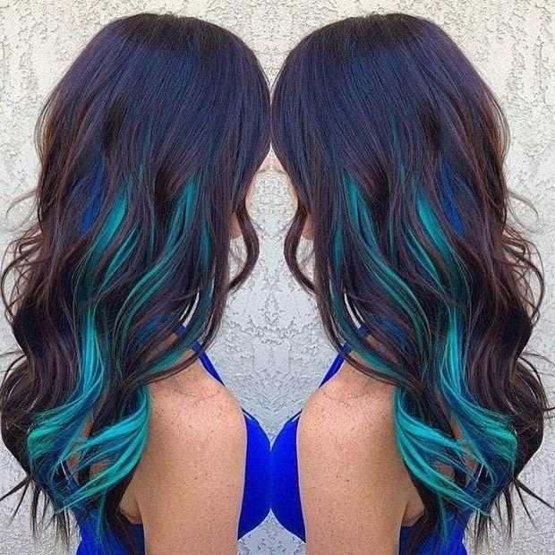 DARK BLUE AND TEAL HIGHLIGHTS: Opt for dark blue and teal highlights if you want to test-drive the blue look before dyeing your whole hair. This color combination is perfect for women with natural dark hair.