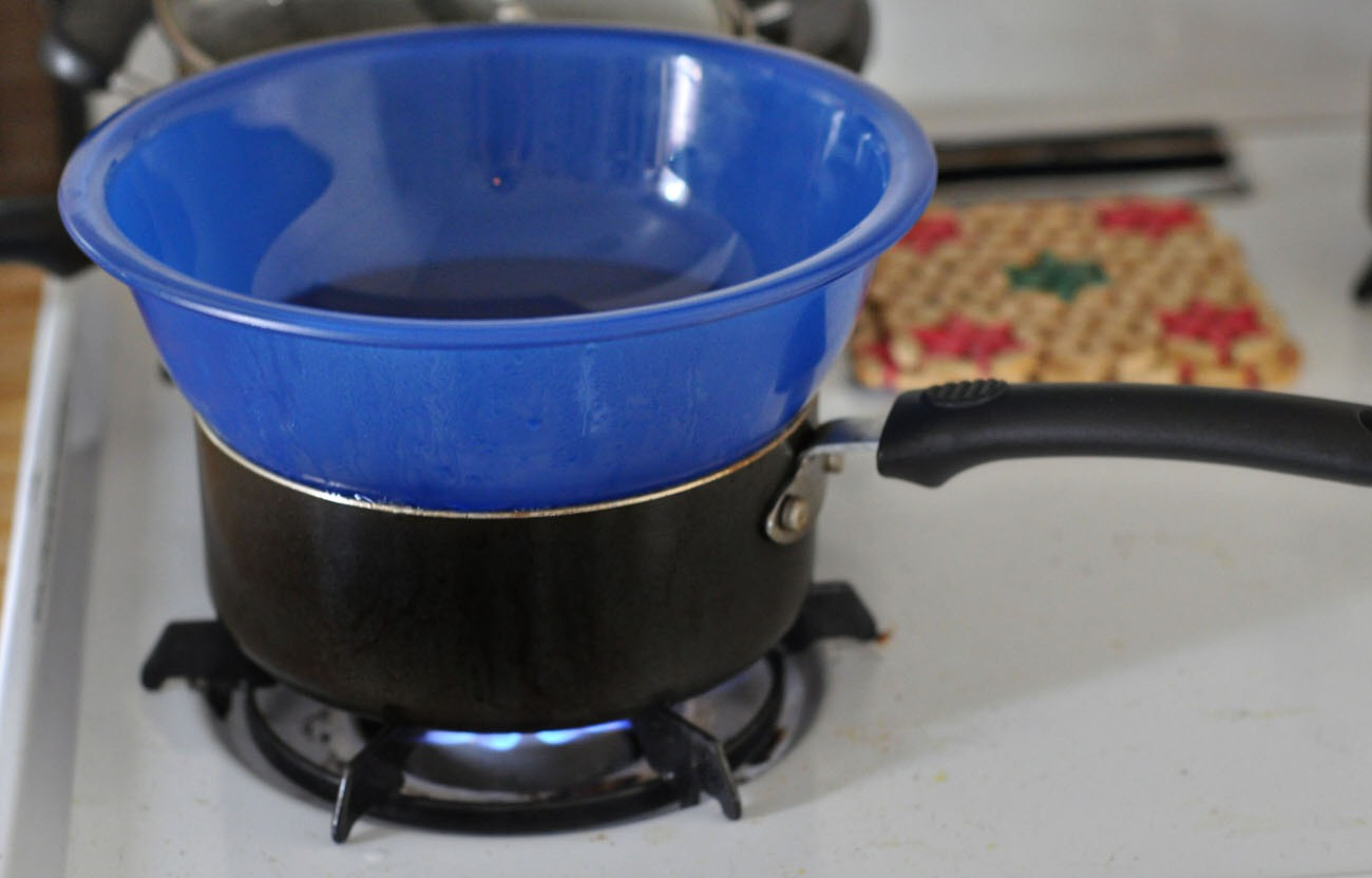 place a bowl over a pot of boiling water and add half of the crayon and the half teaspoon of coconut oil and mix until melted