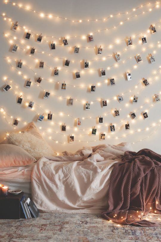 Troubled by a big blank wall? Cover it with twinkle lights and use clothespins to attach treasured photos, as seen on theUrban Outfittersblog.