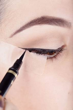 First put a piece of tape big enough to reach the end of your eye to the top of the end of your eyebrows Second gently put on the tape and don't press to hard (or it will hurt when you take it out)  Third color in from the end of your eye to the desired wing lengh