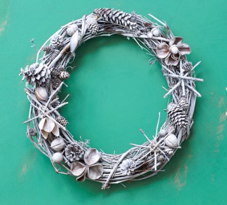 """Use hot-glue to adhere acorns, sticks, pinecones, and walnuts to a 16"""" grapevine wreath. Apply a light coat of white spray-paint to create a frosted finish."""