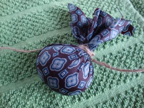 Tie it snug with a piece of string. Make sure to smooth out the silk as best you can. The pattern will transfer only where it is touching the egg.
