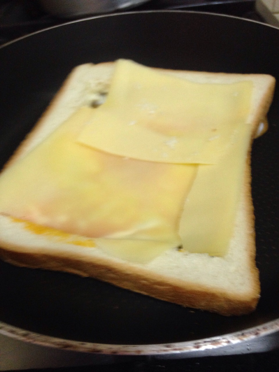 Add a slice or two of cheese to cover the eggs
