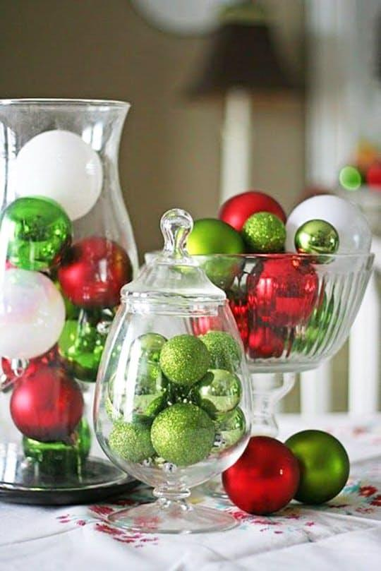 There are so many great centerpiece ideas that involve ornaments, and you likely have some extras laying around after trimming the tree. Here are a few simple ones that you can pull together easily and quickly.Fill up some glass vases and bowls with ornaments like this display fromV and Co.