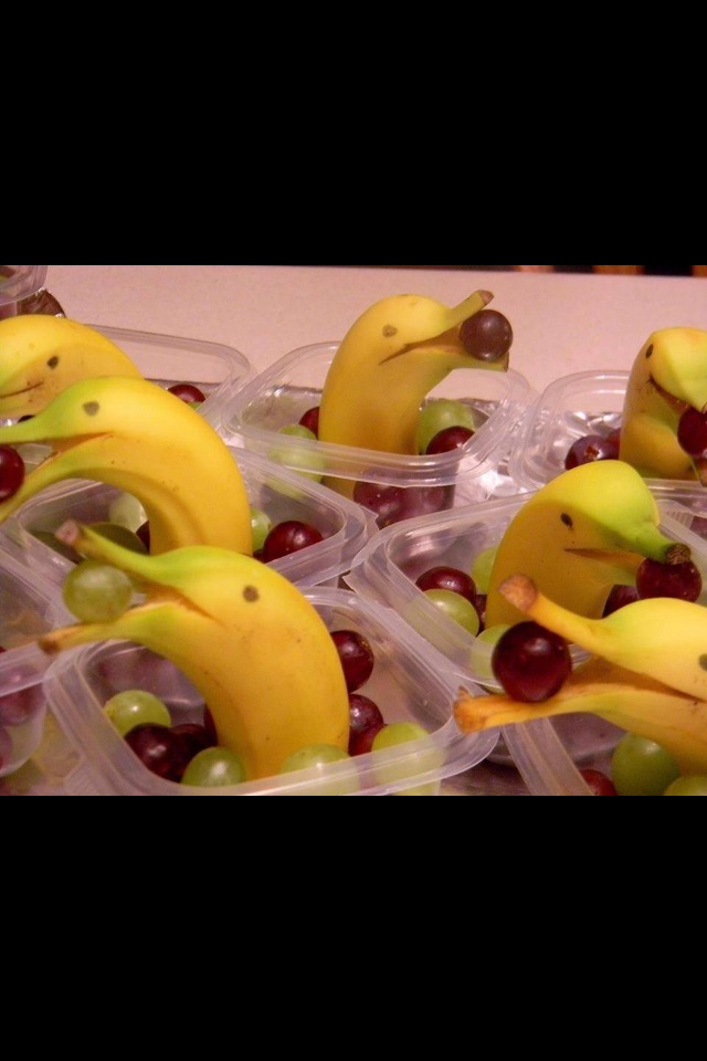 Half the bananas, snip the tips enough to fit in a grape. Place the banana in first then top up with grapes or other fruits. Add eyes to the banana skin. Great party idea instead of sweets and chocolate.