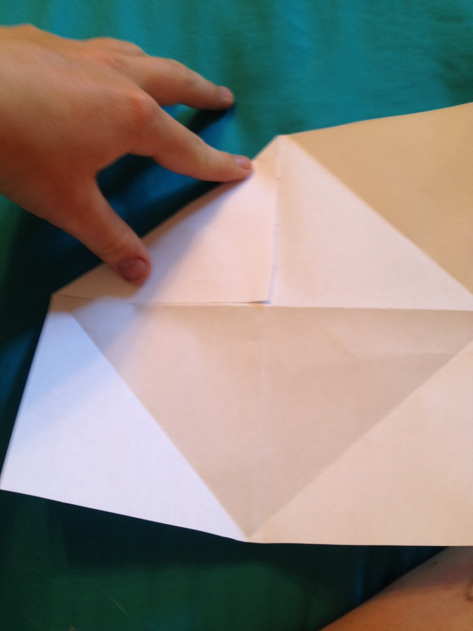 Fold in all corners to the center