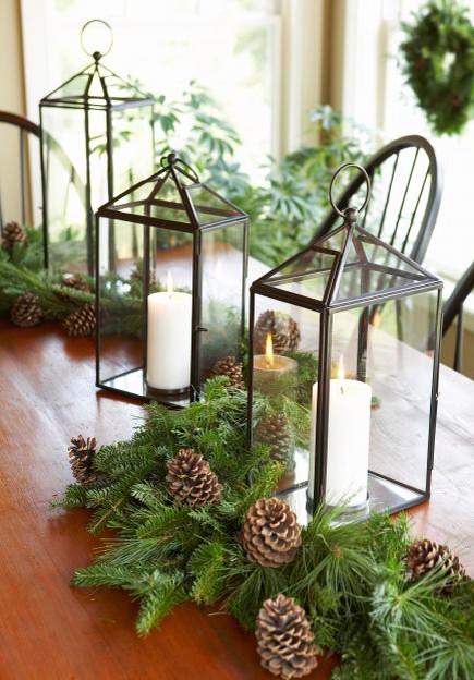 Lantern light  Surround lanterns with fresh greenery and pine cones for a classic, elegant centerpiece.