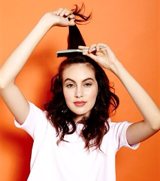 Begin with textured hair. For extra lift, grip at the crown and tease lightly all over with a teasing brush.