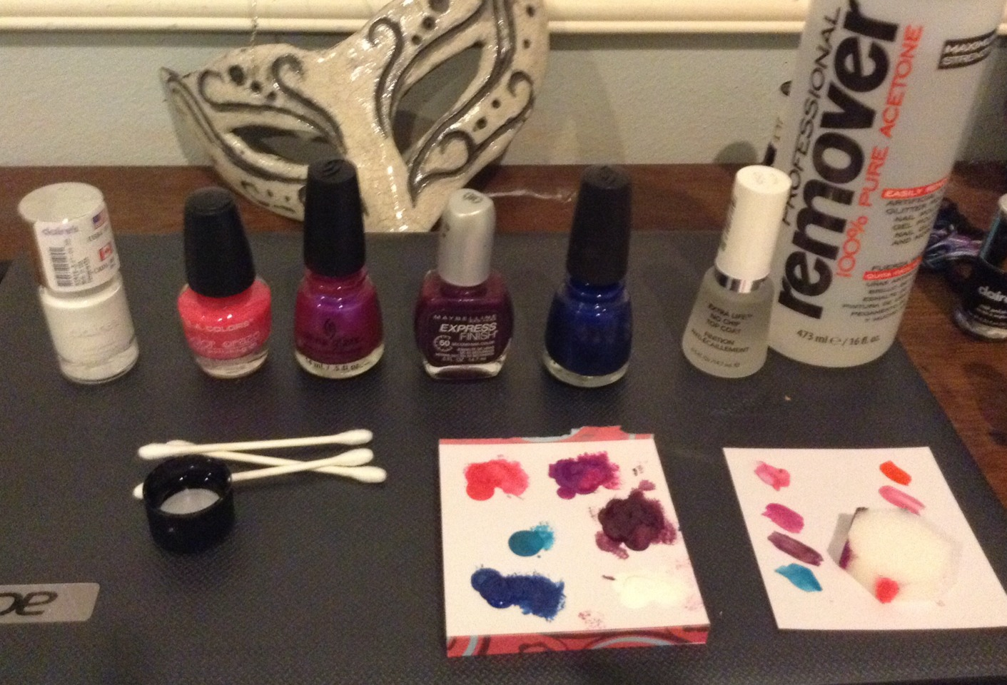 Things you need, pink, light purple, dark purple, dark blue, and white nail polish. A sponge, acetone or nail polish remover, Q-tips and something to put the polish on