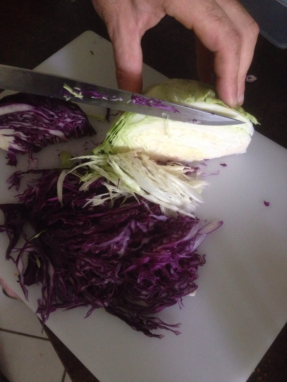 Finely shave of slices of cabbage use both quarters and chuck in a large bowl.
