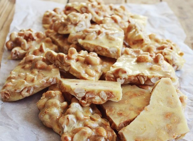 Remove from heat and stir in vanilla extract and peanuts. Then stir in the baking soda (this will cause the mixture to foam). Quickly pour the mixture out onto a silpat mat or a baking sheet lined with parchment paper.