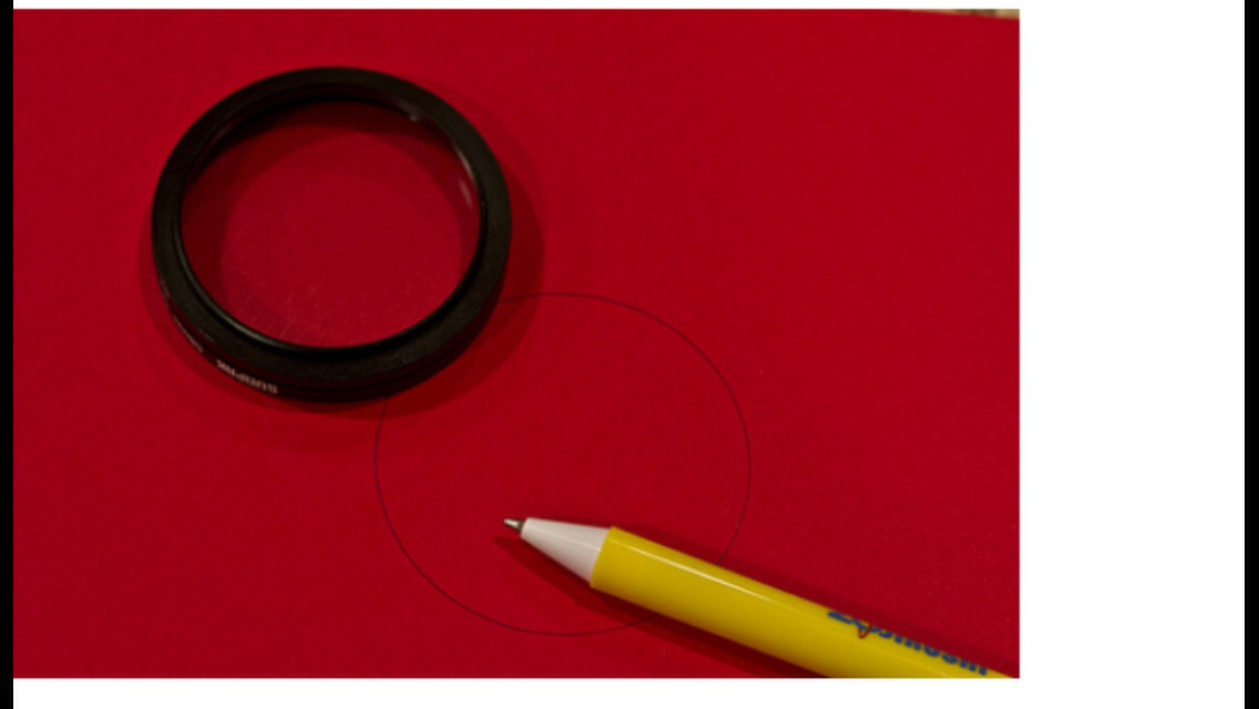 Take a piece of dark coloured card stock and draw a circle on it (or outline your lens)