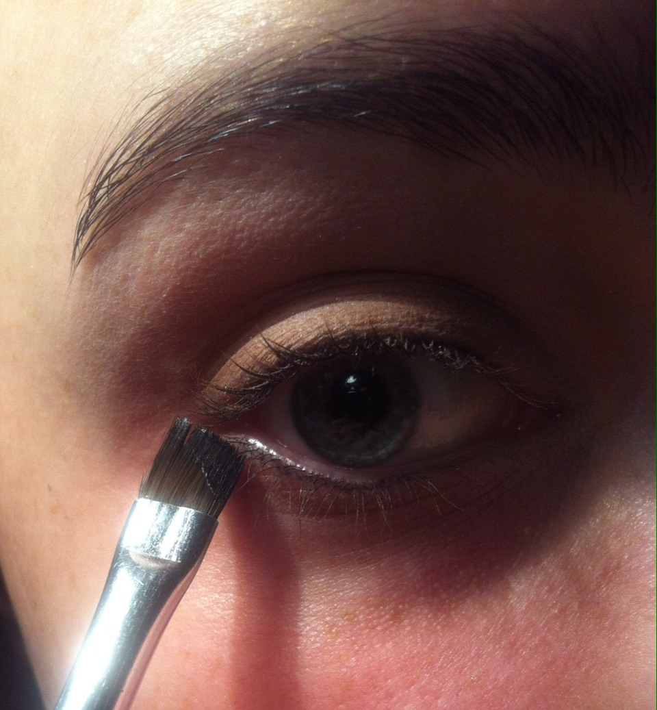 To get the eyeliner flick at the right angle, move the brush so that it's in a straight line with your bottom lid. This makes it even and balanced.