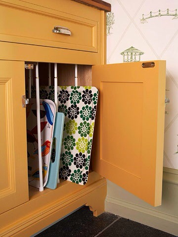 Use Spring Rods as Cupboard Partitions  No place to store trays in your small kitchen? Use spring rods to partition space in a cupboard.