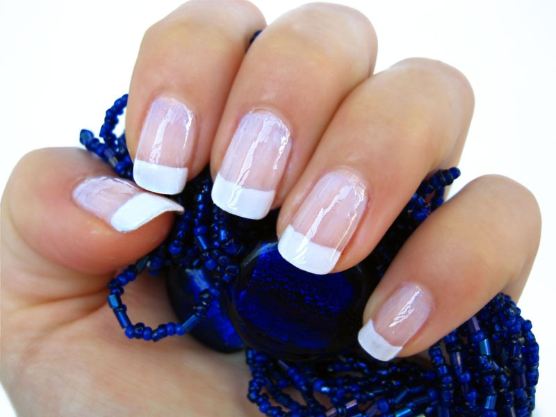 Put scotch tape on the bottom half of my nails. Then, I paint the part above the tape with white polish. As soon as I paint all 10 fingers, I remove the tape, take a clear or sheer pink nail gloss and paint over the whole nail