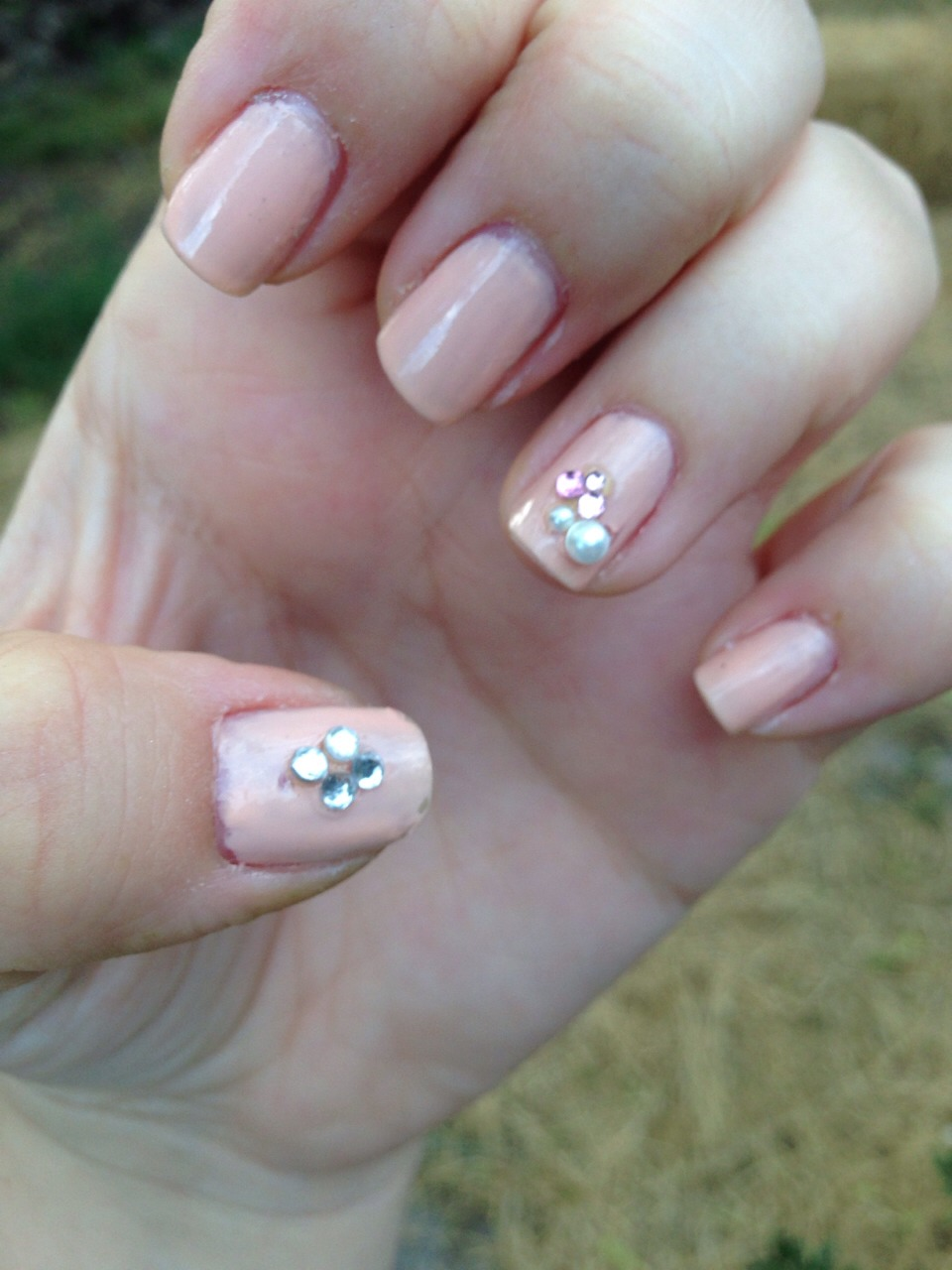 Steps:  1: Paint your nails any color you want and apply a top coat  2: Apply rhinestones and designs with a nail stick (you can buy cheap stick-on rhinestones at walmart)  3: Apply 2 layers of top coat over whole nail including over design  4: Let nails dry 5: Enjoy your almost no cost nails!
