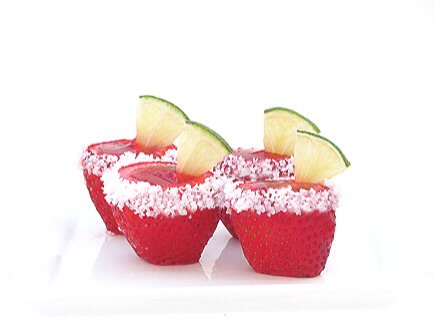 Pour final Jell-o mix into strawberries and chill overnight. Dip your finger in water or use a moistened brush to wet the edge of the strawberries, dip and rotate the strawberries in salt to rim. Garnish with cut lime triangles to finish.