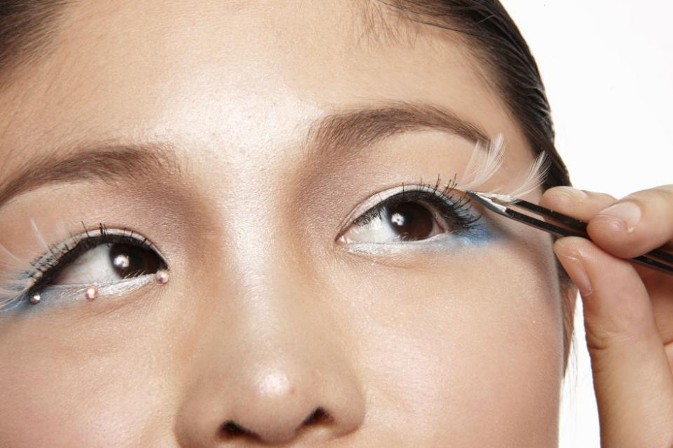 2  Place Lashes Get angelic with feathery white lashes. Cut lash strip in half, then dip it in lash glue. Use tweezers to place it on the outer lash lines.