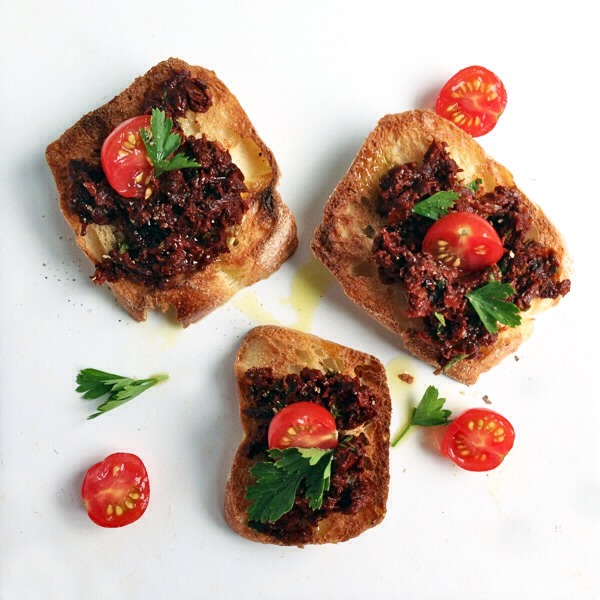Sun-Dried Tomato Crostini  To serve your sun-dried tomato pesto crostini, spread the pesto on toasted baguette slices and garnish with cherry tomato halves, parsley sprigs, and a drizzle of olive oil.