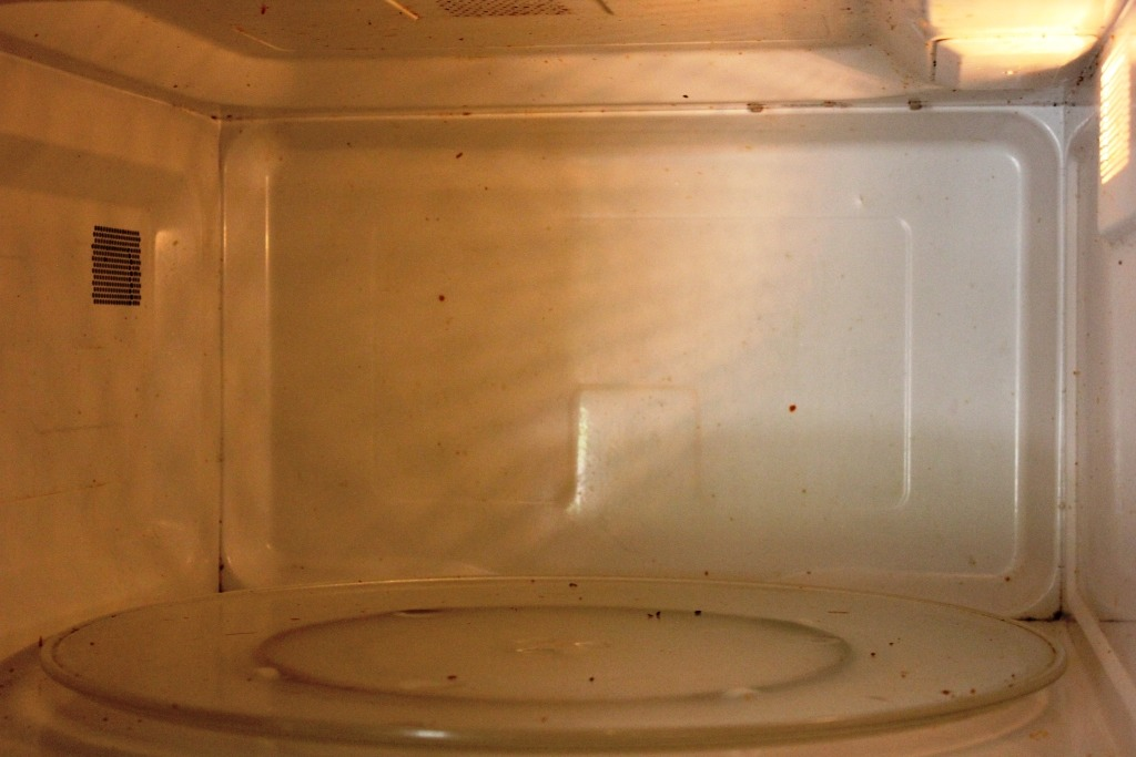 Pour 1 cup of vinegar and 1 cup of water into microwave safe bowl Microwave the mixture on high for 5 minutes.  The vinegar mixture will produce steam which will work to soften the food particles in the microwave. Remove the bowl from the microwave and let it sit for 10 minutes.