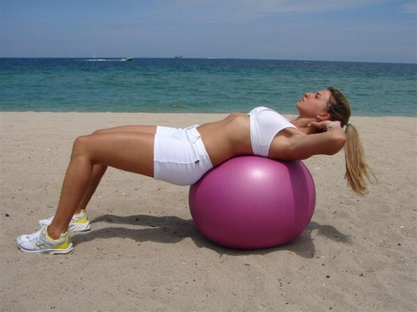 Start sitting upright on top of the inflatable exercise ball, feet flat on the floor, knees in line with your hips. From this position, inhale, engage your abs and lean back so that your body is behind the vertical.