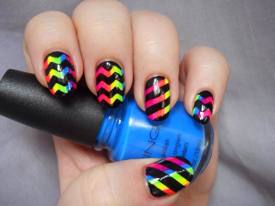 This is actually easy to do! Do your first coat in a rainbow design (do this with a sponge the way you would with ombré nails), allow to completely dry and top with a chevron design in black!