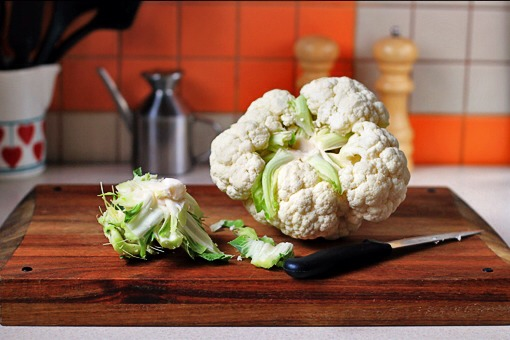Despite their rather impenetrable-seeming appearance, cauliflowers are actually pretty easy to break down into bite-sized florets.  Here's how I do it:  1.First, remove the green leaves and then, using a knife,remove the central stem, too.  Now your cauliflower is ready to be easily cut into pieces.