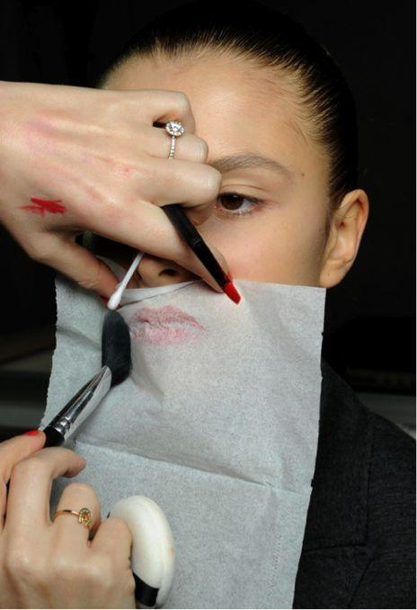 After your lipstick is applied, hold a tissue over your lips and apply powder over the tissue