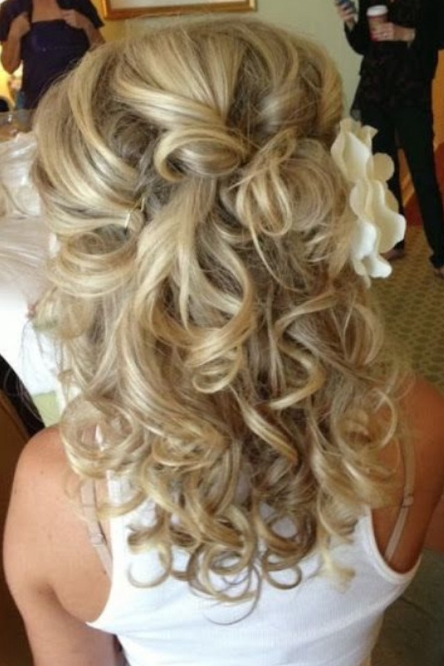 Messy curls with the top pinned with a flower.