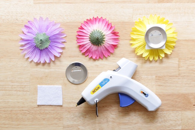 How to Make Boutonnieres  Heat up your glue gun, and cut some white felt into small rectangles. Put some hot glue on a button back and stick a felt rectangle to it. Next, apply a generous layer of hot glue to the other side of the felt and stick a flower top to it. Tightly hold together until dry