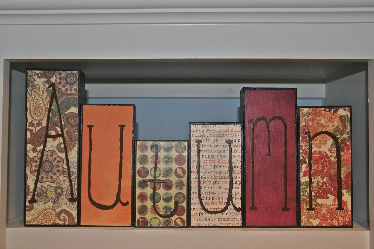 supplies: six large blocks, fall themed scrapbooking paper, sharpie marker, mod podge How to: apply a thin coat of mod podge on the blocks, now lay  the scrapbooking paper over the block and place down, lastly spell out the words autumn on the blocks.