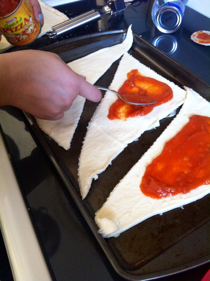 6. Spread pizza sauce on the dough, (mainly in the middle otherwise it'll overflow!)