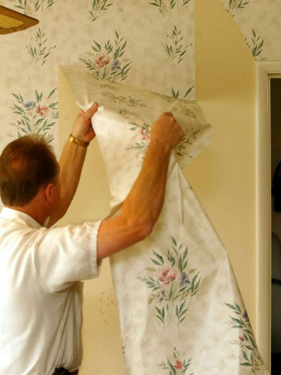 Peel the top layer of the wall paper off leaving the backing stuck to the wall.