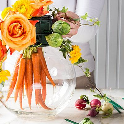 Gather carrots and rest florist foam square on top of fishbowl, allowing the carrots to hang down inside fishbowl.