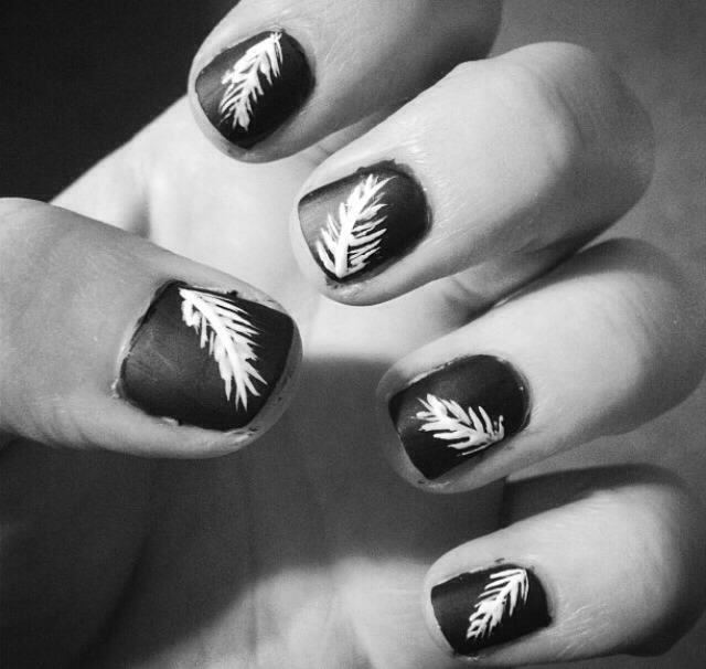 To get these nails... 1) paint nails a dark color and let dry 2) use a white nail striper to paint a white curve from the corner of the nail and flick outward 3) draw tiny wispy curves around the bigger curve so that it begins to look like a feather 4) use a matte top coat and you're good to go