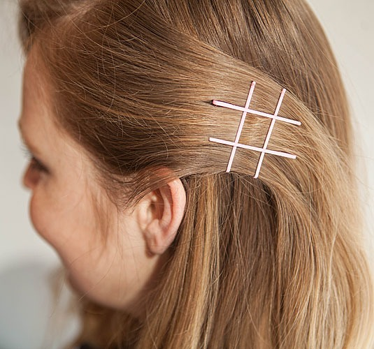9. Try the exposed bobby pin trend with #fun designs. Pin back a section of hair with two bobby pins in an upward direction. Complete the hashtag by inserting two more bobby pins perpendicular to the first two.