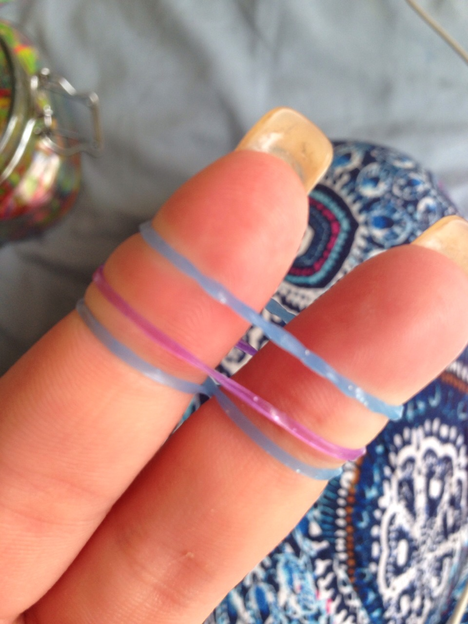 Take the third band and place over fingers like the purple band