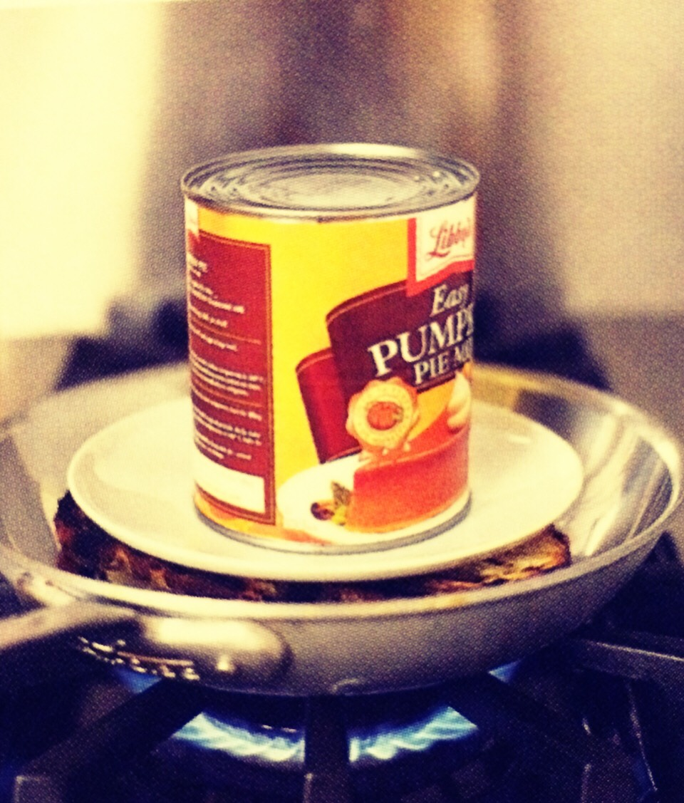 Put the heatproof dinner plate and the can of vegetables on top of your buttered sandwich as it cooks in the frying pan over medium heat.
