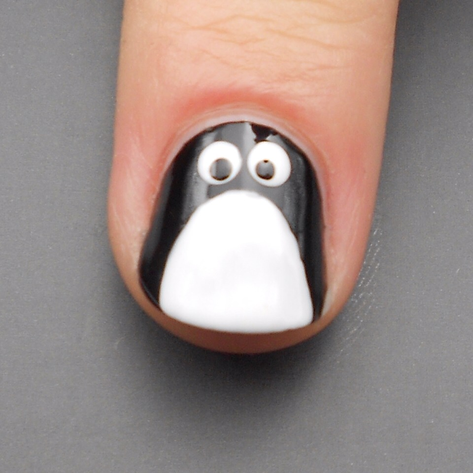 Step 4:  Take a small dotting tool or toothpick dipped in your black polish and create the two pupils in the eyes.