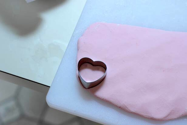 "Using heart-shaped cookie cutters, stamp hearts from the dough. Although they can be made any size, a 1 ½""-1 ¾"" candy is closest the the familiar candy size. We used both 1 ¾"" and 2 ½"" cutters to create our homemade hearts."