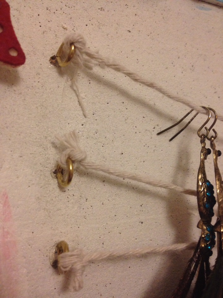 pop in some small hooks or screw loops, use a hot glue gun to secure them in place and then tie some string between them like a washing line to hang your dangly earrings on