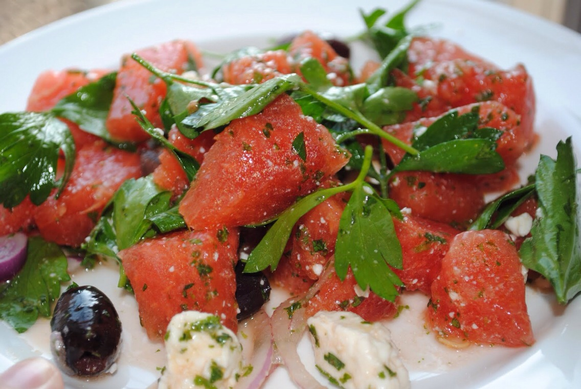 1 small Red Onion  2 - 4 Lime depending on the juiciness  1.5 kg sweet, ripe Watermelon  250 g Feta cheese  fresh Flat-leaf parsley  fresh Mint chopped  4 tablespoons Extra Virgin Olive Oil  100 g pitted Black Olives  Black pepper