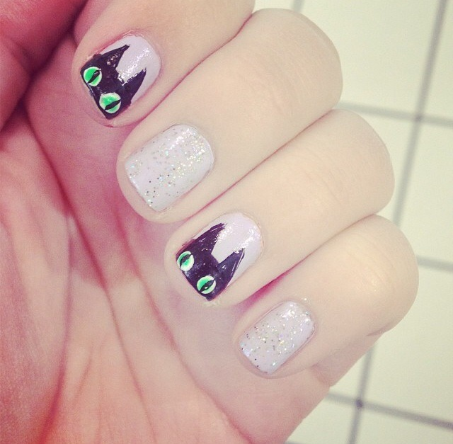 Paint nails any light color and then paint a black semicircle at the tips of nails where you want the black cats. Use a black striper to paint little triangles for ears. Using a dotting tool, place dots of white for eyes and then bright green to make them pop. Draw a thin black line for the pupils(: