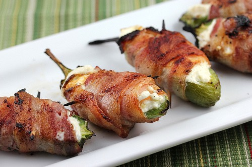 Preheat oven to 400 degrees F (200 degrees C). Line a baking sheet with aluminum foil. Mix cream cheese and Cheddar cheese together in a bowl until evenly blended. Fill each jalapeno half with the cheese mixture. Put halves back together and wrap each stuffed pepper with a slice of bacon. Arrange ba
