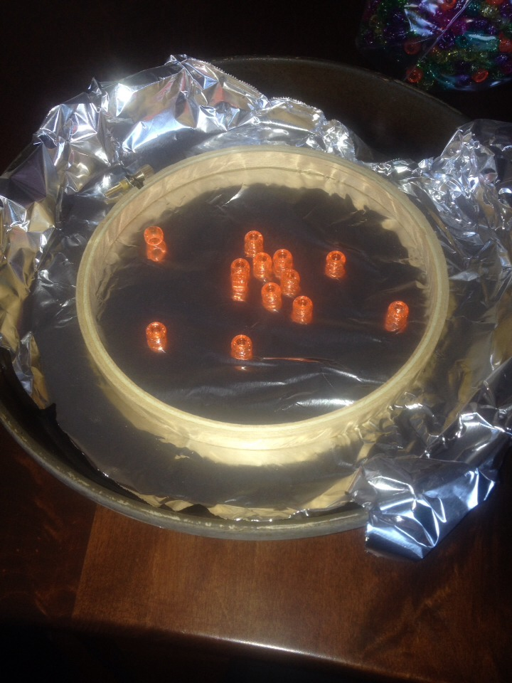 Put an embroidery hoop in a cake pan lined with foil, then start adding plastic beads