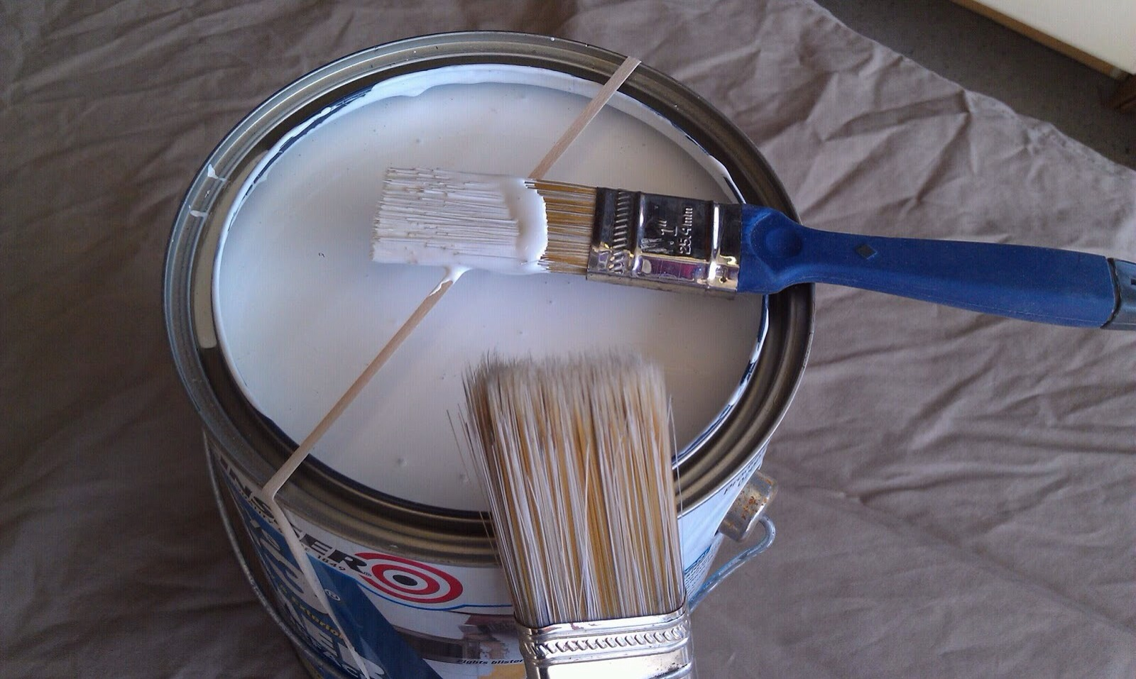 Place a rubber band around an open tin of paint to wipe the brush on and avoid getting paint on the edges on the tin.