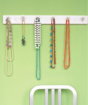 Use an old coat rack paint it whatever color you like and hang your fav necklaces for all to see.