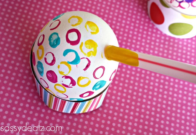 Have the kids dip the end of the straw into the paint and press it on the egg, making a turning motion.