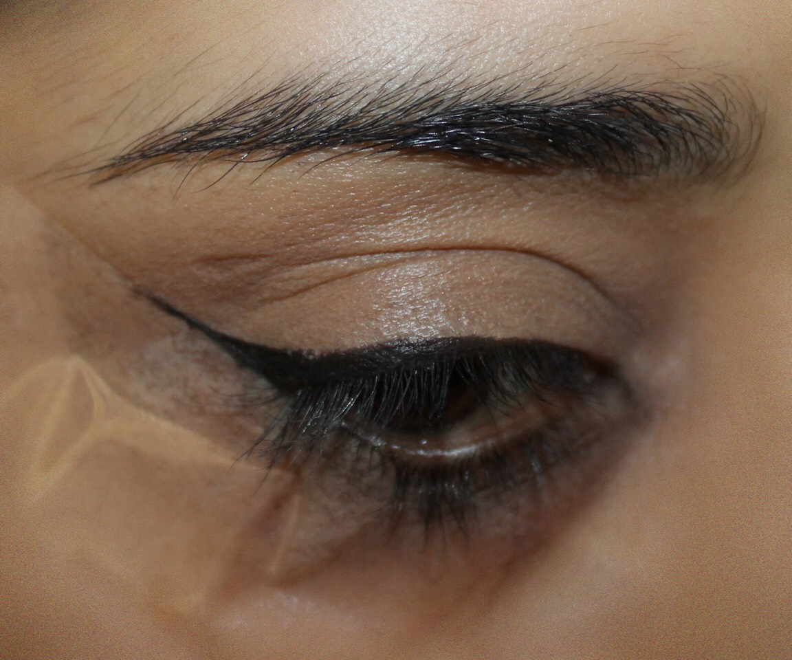 Stick strips of sellotape on the back of hands three times then apply the same sellotape strip below the eye in line with the end of the eyebrow (as above) and draw equals flicks of both sides, this will give a no wobble effect.