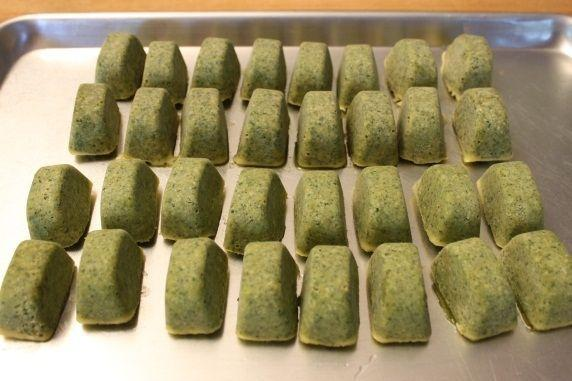 I flip the ice cube tray over and put it under the the faucet to trickle some cold water on the bottom of the tray for a few seconds--hold your hand underneath the tray so the cubes don't fall into the sink. The pesto cubes pop right out.